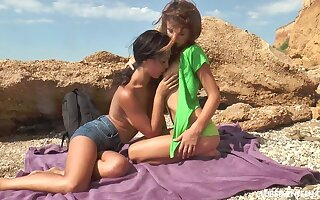 Two gorgeous teens conclave out on the beach